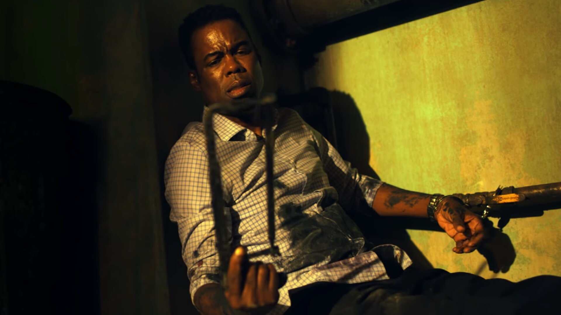 Chris Rock as Detective Banks in Spiral: From the Book of Saw. Det. Banks is slumped in a darkened room, handcuffed by one arm to a pipe, mirroring the trap from the first film. In his other hand he holds a saw, which he stares down at.